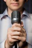 Micrófono en manos del hombre, foco en los dedos Fotos de archivo