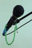 Micrófono en un fondo y un rosario verdes Fotografía de archivo libre de regalías