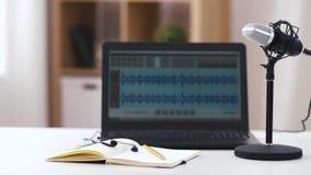 Micrófono, ordenador portátil, auriculares en el cuaderno en la tabla metrajes