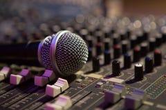 Micrófono que descansa sobre una consola de los sonidos Fotos de archivo libres de regalías
