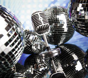 Micrófono retro del estilo en ondas acústicas y bolas de discoteca Fotos de archivo