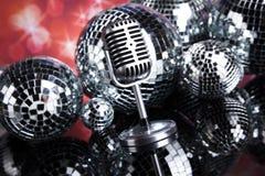 Micrófono retro del estilo en ondas acústicas y bolas de discoteca Foto de archivo