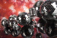 Micrófono retro del estilo en ondas acústicas y bolas de discoteca Imagen de archivo libre de regalías