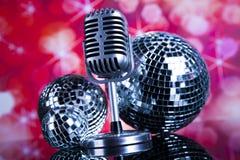 Micrófono retro del estilo en ondas acústicas y bolas de discoteca Imágenes de archivo libres de regalías