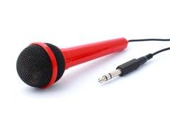 Micrófono rojo con el enchufe y el cable aislados imágenes de archivo libres de regalías