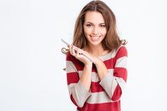 Micrófono sonriente de la cubierta de la mujer en smartphone con la palma Imagenes de archivo