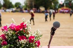 Micrófono vocal en foco agudo contra la audiencia borrosa Imagenes de archivo