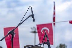Micrófonos negros en una etapa en la etapa del concierto del carnaval anaranjado del flor delante de la bandera turca en el 5 de imagenes de archivo