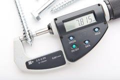 Micrómetro de Digitaces con la medida ajustable de la presión con los tornillos de acero aislados en el fondo blanco Imagen de archivo