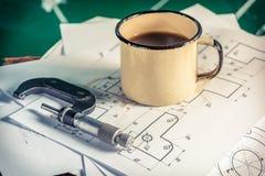 Micrômetros, diagramas mecânicos e uma xícara de café foto de stock