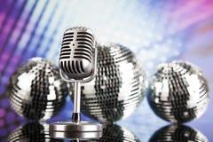 Micrófono retro del estilo en ondas acústicas y bolas de discoteca Imagen de archivo