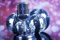 Micrófono retro del estilo en ondas acústicas y bolas de discoteca Fotos de archivo libres de regalías