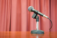 Micro_2. Photograph of microphone in front of a red curtain Stock Photos