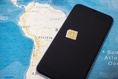 Micro SIM card and smartphone on the world map stock images