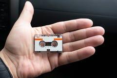 Micro taglio del fondo dell'audio cassetta a disposizione fotografia stock libera da diritti