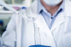 Microbiologist hand cultivating whit inoculation loops in pipette close-up. Stock Photos