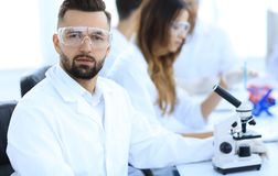 Microbiologist and his colleagues are sitting in a modern laboratory Royalty Free Stock Images