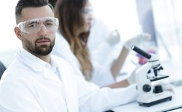 Microbiologist and his colleagues are sitting in a modern laboratory. Young, microbiologist and his colleagues are sitting in a modern laboratory Stock Image