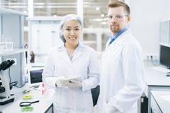 Microbiologistes de sourire se tenant dans le laboratoire avec le comprimé photos libres de droits