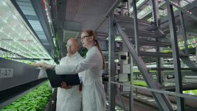 Microbiologists man and woman on the production of hydroponics in white coats, a man holding a laptop, a woman hands