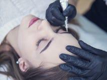 Microblading在美容院的眼眉工作流 浅褐色的女孩做眼眉needle 免版税库存图片