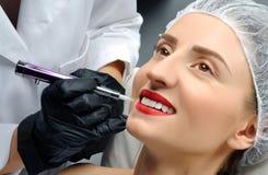Microblading 做永久性的美容师构成 得到面部关心和纹身花刺的可爱的妇女 库存照片