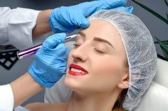 Microblading Cosmetologist die permanente make-up maakt Aantrekkelijke vrouw die gezichtszorg en tatoegeringswenkbrauwen krijgen stock foto