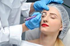 Microblading Cosmetologist die permanente make-up maakt Aantrekkelijke vrouw die gezichtszorg en tatoegeringswenkbrauwen krijgen stock afbeeldingen