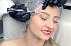Microblading Cosmetologist effectuant le renivellement permanent Femme attirante obtenant les sourcils faciaux de soin et de tato photo libre de droits