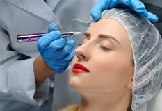 Microblading cosmetologist makeup που κάνει μόνιμο Ελκυστική γυναίκα που παίρνει τα του προσώπου φρύδια προσοχής και δερματοστιξι στοκ εικόνα με δικαίωμα ελεύθερης χρήσης
