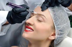 Microblading cosmetologist makeup που κάνει μόνιμο Ελκυστική γυναίκα που παίρνει τα του προσώπου φρύδια προσοχής και δερματοστιξι στοκ φωτογραφίες με δικαίωμα ελεύθερης χρήσης