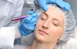 Microblading. Cosmetologist making permanent makeup. Attractive woman getting facial care and tattoo eyebrows. Microblading eyebrows. Cosmetologist making royalty free stock image