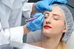Microblading. Cosmetologist making permanent makeup. Attractive woman getting facial care and tattoo eyebrows. Microblading eyebrows. Cosmetologist making stock images