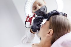 Microblading eyebrows work flow in a beauty salon. Woman having her eye brows tinted.  royalty free stock image