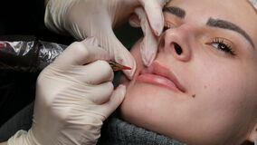 Microblading lip tattoo with a special coloring red pigment that corrects lip color in a cosmetology clinic. Permanent