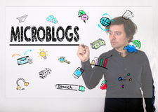 Microblogs concept. Businessman writing with black marker on vis Stock Photo