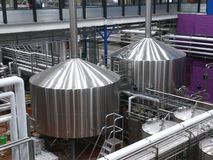 Microbrewery. Pipes and large vats in a microbrewery are shown Stock Image