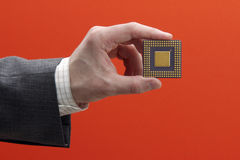 Microchip. Hand with microprocessor on a red background Royalty Free Stock Photos