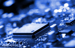 Microchip on blue circuit board. Close-up microchip on circuit board, blue toning Stock Images