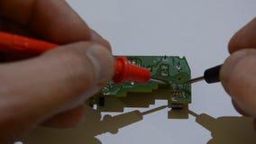 Microchip principal de las pruebas y de las reparaciones del ingeniero con el multímetro almacen de video