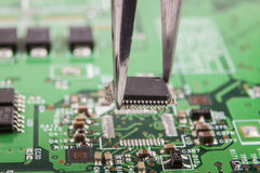 Microchip Removal. Mounting microchip on green electronic circuit board with tweezers royalty free stock photography