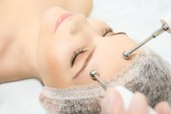 Microcurrent facial dermatology procedure. Model. Aesthetic radiofrequency treatment. Micro current cosmetology massage.  stock images