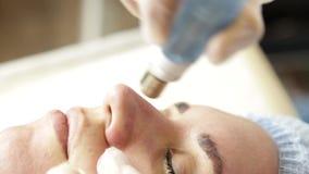 Microdermabrasion διαμαντιών, επεξεργασία ξεφλουδίσματος cosmetic beauty spa στην κλινική γυναίκα που παίρνει ένα κενό microderma φιλμ μικρού μήκους