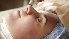 Microdermabrasion del diamante, pelando el tratamiento en la clínica cosmética del balneario de la belleza mujer que consigue un  almacen de video
