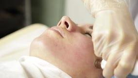 Microdermabrasion del diamante, pelando el tratamiento en la clínica cosmética del balneario de la belleza mujer que consigue un  metrajes
