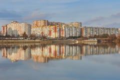 Microdistrict en el oeste de Krasnodar y su reflexión en el río de Kuban en la puesta del sol imagenes de archivo