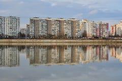 Microdistrict i det västra av Krasnodar och dess reflexion i den Kuban floden på solnedgången Två världar i ett ställe royaltyfria bilder