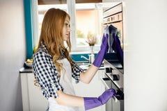 与microfiber旧布的美好的白肤金发的妇女清洁在微波炉外面 免版税库存图片