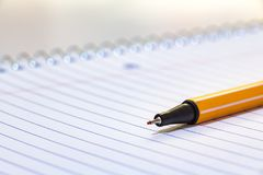 A microfiber plastic pencil on a notebook with spiral. A plastic microfiber pencil on the corner of a notebook with spiral, closeup Royalty Free Stock Image