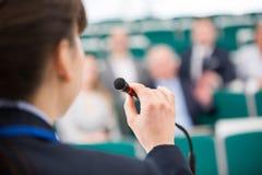 Microfone de Giving Speech On da mulher de negócios na sala de leitura foto de stock royalty free